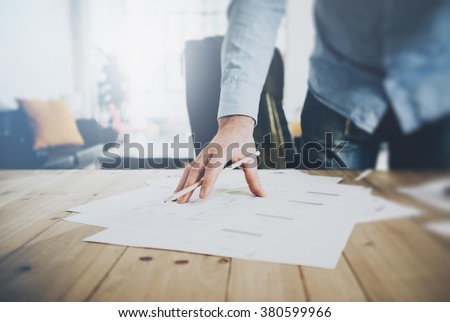 Businessman at work. Holding pencil in his hand. Architectural project on table. Blurred background, horizontal mockup.