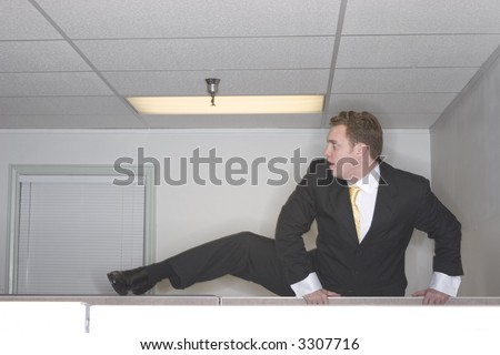 Businessman attempts to climb over his cubicle trying to escape out of his office while wearing a black suit