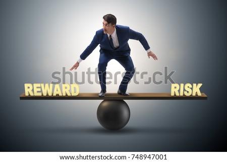 Businessman balancing between reward and risk business concept