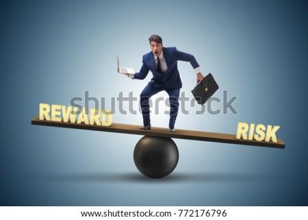 Businessman balancing between reward and risk business concept #772176796