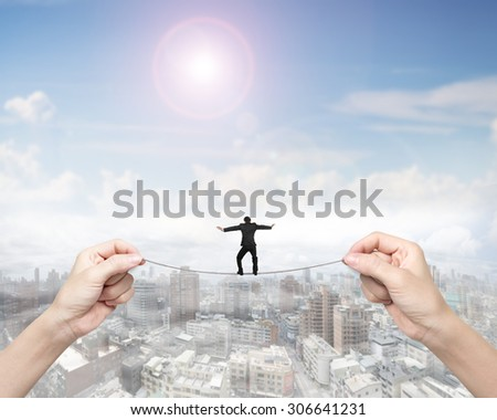 Businessman balancing on tightrope with woman two hands holding two sides, on sunny sky cityscape background.