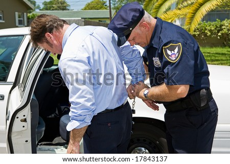 Businessman being handcuffed and placed under arrest.