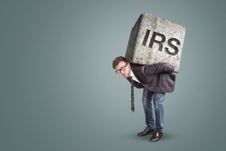 Businessman bending under a heavy stone with the letters IRS printed on it - tax office concept