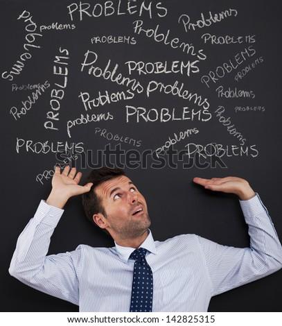 Businessman bending under stack of problems