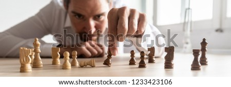 Businessman brainstorming as he creates business strategy by placing black and white chess pieces on office desk. #1233423106