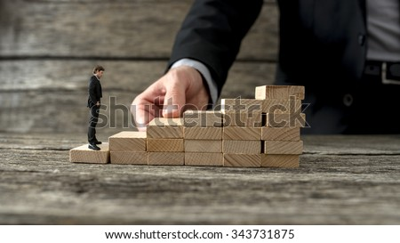 Businessman building a staircase of wooden pegs for another entrepreneur to climb up the ladder of success.