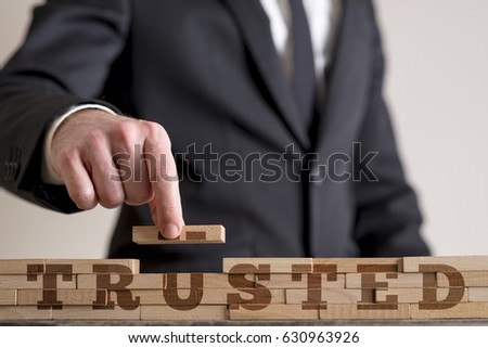 Businessman building a structure of wooden dominos while assembling word Trusted. #630963926