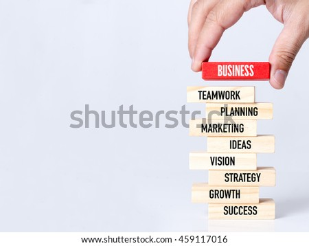 Businessman Building BUSINESS concept with Wooden Blocks