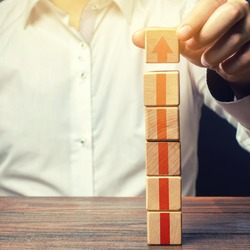 Businessman builds a tower of blocks with an up arrow. Career promotion, growth of professional skills. Profit growth. Marketing. Improving efficiency. Business development, expansion improvement.