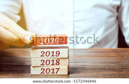 Businessman builds wooden blocks 2020. The concept of the beginning of the new year. New goals. Next decade. Trends and changes in the world. Build plans and planning. Time report #1572346846