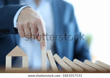 Businessman built house from wooden blocks. Real estate accident insurance concept Stockfoto ©