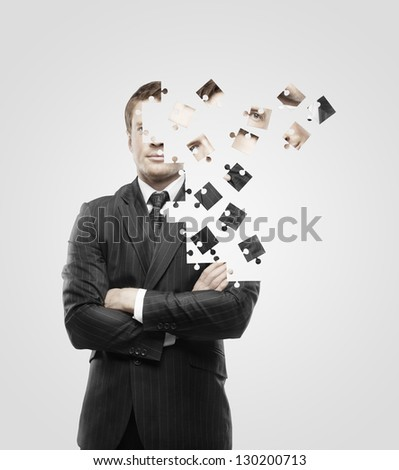 businessman built of puzzle on white background