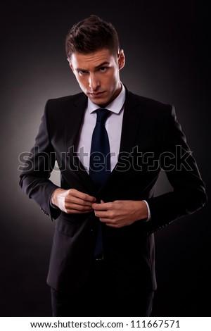 businessman buttoning jacket, getting dressed, on dark background