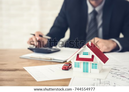 Businessman calculating budget before signing real estate project contract with house and car model at the table in the office