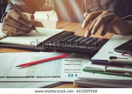 Businessman Calculating Invoices Using Calculator