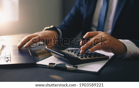 Businessman calculating the financial statement of his business. Accounting and Tax. Stockfoto ©