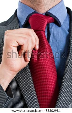 Businessman carefully adjusting his tie