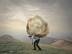 Businessman carrying a big rock