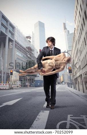 Businessman carrying a mannequin on a city street - stock photo