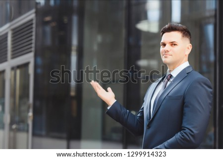 Businessman caucasian in blue suit shows his right hand on copy space. Copy space left.