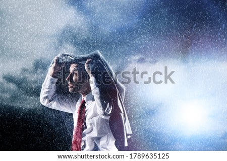 Photo of  Businessman Caught in heavy Rain hiding under his jacket