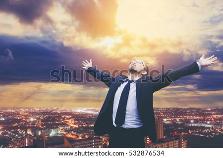 businessman celebrates freedom success arms raised looking up to sky. Positive human emotions face expression feelings. city background.