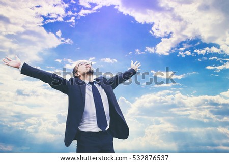 businessman celebrates freedom success arms raised looking up to sky. Positive human emotions face expression feelings.