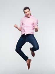 Businessman celebrating his success and jumping over gray background. Looking at camera