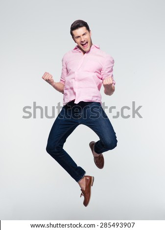 Businessman celebrating his success and jumping over gray background. Looking at camera #285493907
