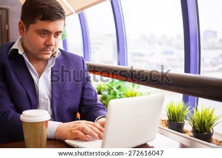 businessman check his email on the computer in a cafe
