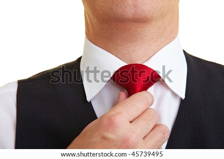 Businessman checking his tie knot with his hand