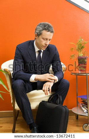 Businessman checking his watch while waiting - stock photo