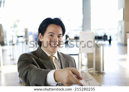 Businessman checking in at airport, receiving boarding pass from check-in attendant, smiling, portrait, view from behind check-in desk (differential focus)