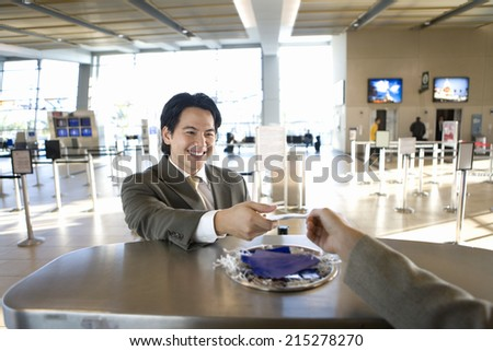 Businessman checking in at airport, receiving boarding pass from check-in attendant, view from behind check-in desk