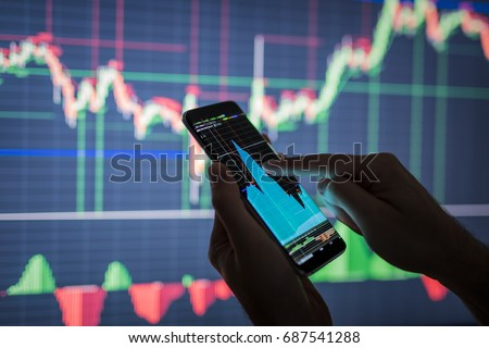 Businessman checking stock market data. He using a mobile phone. Analysis economy data on forex earn graph.  Foto d'archivio ©