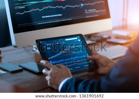 Businessman checking stock market on digital tablet and a desktop computer with stock exchange graph on screen. Financial stock market. Analyzing data in office background.