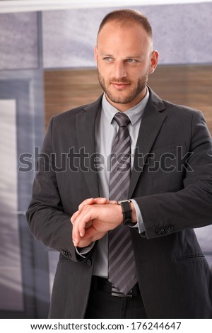 Businessman checking time on wristwatch, waiting, standing.