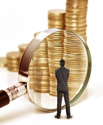 Businessman checks the money with magnifying glass