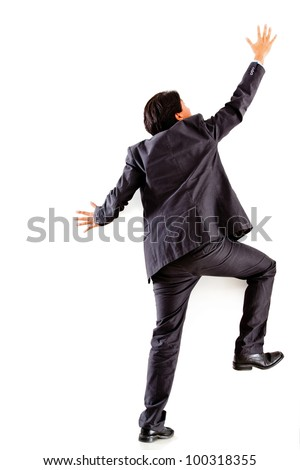 Businessman climbing a wall - isolated over a white background - stock photo