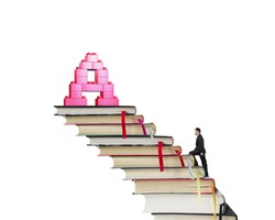 Businessman climbing books stairs toward alphabet letter A shape stack blocks, isolated on white background.