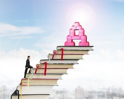 Businessman climbing books stairs toward alphabet letter A shape stack blocks, with sunny sky cityscape background.