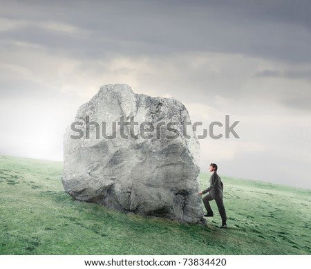 Businessman climbing on a rock on a green meadow