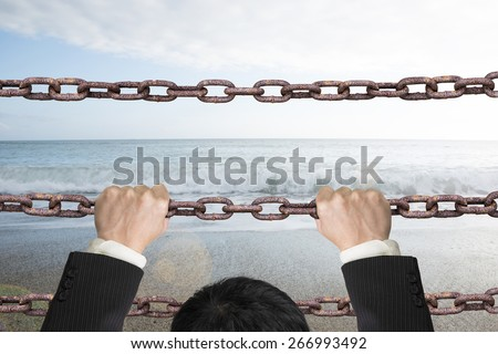 Businessman climbing on old iron chains to go out with natural sky sea background