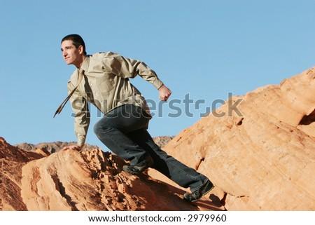 Businessman climbing on red rocks