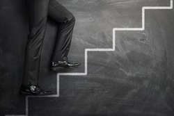 Businessman climbing the career stairs drawn on a chalkboard with copy space