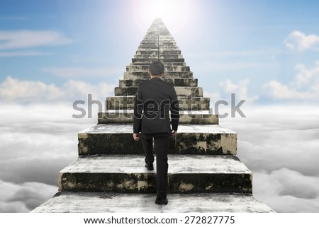 Businessman climbing the old concrete stairs with sky cloudscape sunlight background