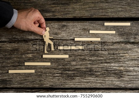 Businessman climbing the steps to success in a conceptual image with paper silhouette cutouts of a man and a human hand helping him climb over rustic wood with copy space. #755290600