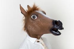 Businessman closeup portrait wearing horse head