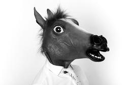 Businessman closeup portrait wearing horse head black and white
