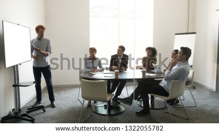 Businessman coach leader giving presentation on mock up white tv screen at team business conference meeting, male speaker presenter training employees group with blank display at workshop training